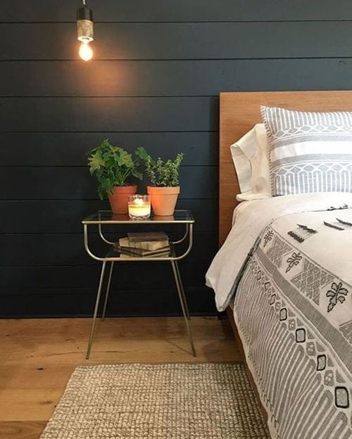 Black smooth shiplap accent wall in bedroom by Joanna Gaines