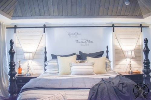 Rustic white shiplap barn doors and charred ash gray on the ceiling of bedroom