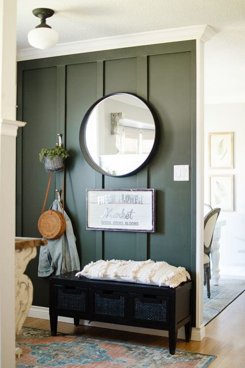 Emerald green board and batten full wall entryway with round mirror and bench