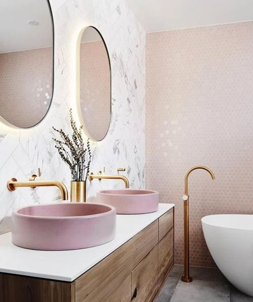Bold light pink bathroom with pink wash basin, white accents, and gold fixtures